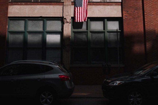 street photo of brick city building with two cars parked in shadows and american flag hanging from building in the sun above