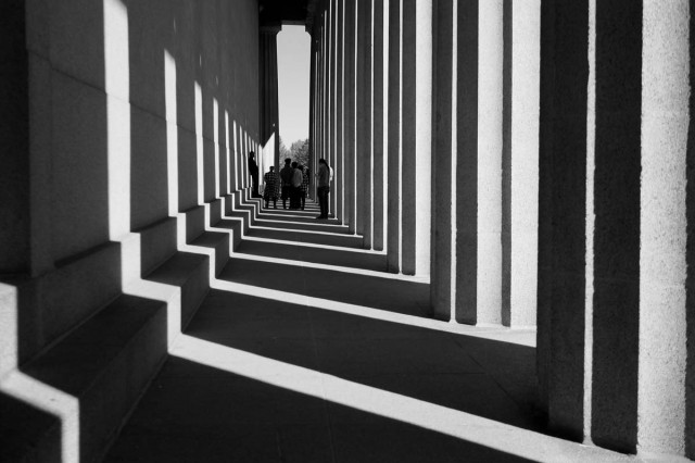 black and white outdoor shot of building pathway with light streaming through large pillars on the right