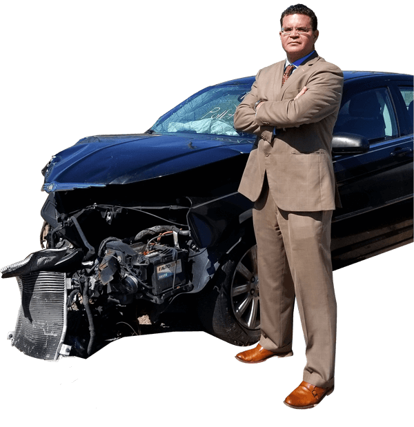 ivan lopez in beige suit with arms crossed standing in front of wrecked car